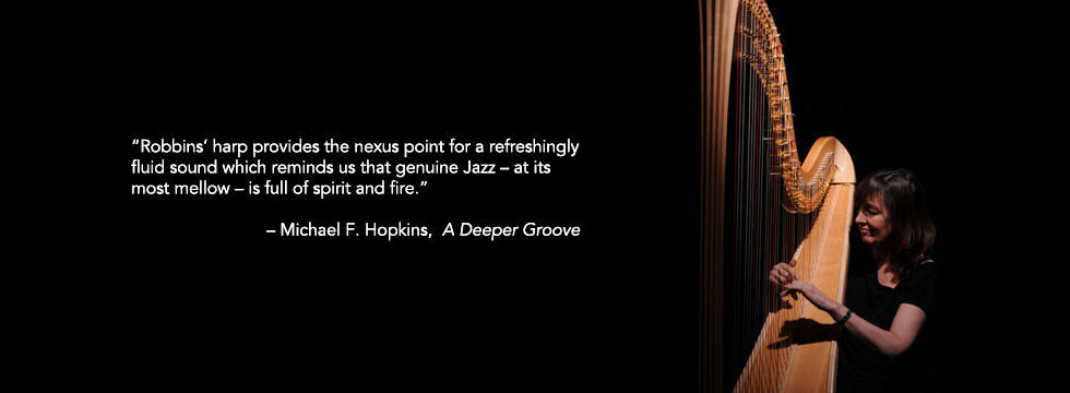 Photo of Carol Robbins playing harp plus review quote by Michael F. Hopkins